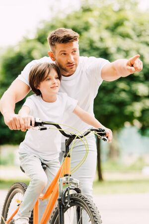 father and son looking forward while kid riding bicycle and dad pointing with finger