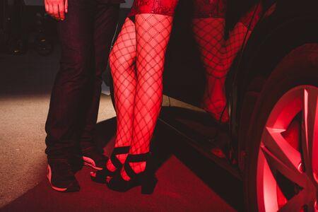 vista ritagliata della donna in gonna rossa e calze a rete in piedi con l'uomo vicino alla macchina