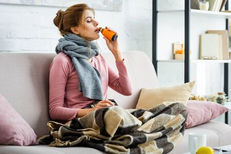 attractive and ill woman with grey scarf drinking cough syrup