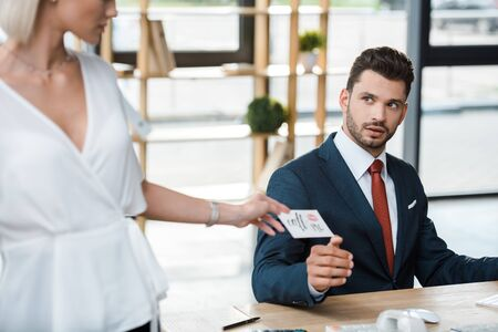 cropped view of blonde woman holding card with call me lettering near surprised businessman Foto de archivo