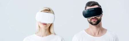 panoramic shot of man and girl in Virtual reality headsets isolated on grey