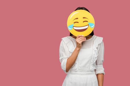 woman covering face with smiley isolated on pink Stock Photo