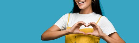 panoramic shot of happy young woman showing heart with hands isolated on blue