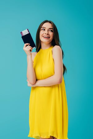 happy brunette woman in yellow dress holding passport with air ticket isolated on turquoise Zdjęcie Seryjne
