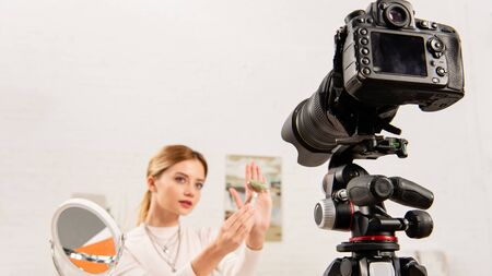 beauty blogger showing jade roller in front of video camera
