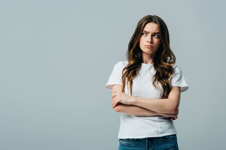 upset beautiful girl in white t-shirt with crossed arms looking away isolated on grey Stockfoto