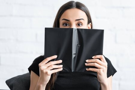scared young woman suffering from dementia covering face with notebook and looking at camera Stock fotó