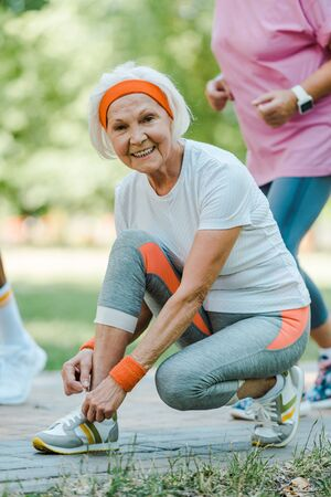 selective focus of happy senior woman sitting and tying shoelaces in park