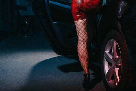 Ausgeschnittene Ansicht einer Frau im roten Rock, die in der Nähe der Autotür steht, während sie im Auto sitzt Standard-Bild