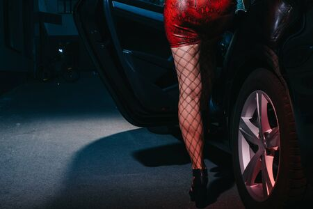 cropped view of woman in red skirt standing near car door while sitting in car Stock fotó