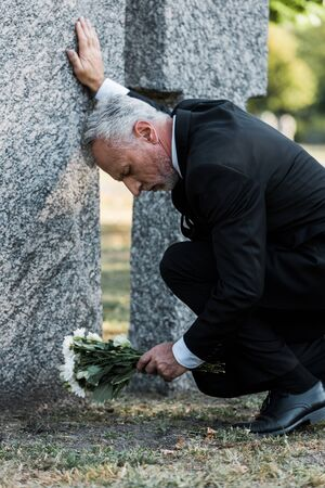 sad man with grey hair putting flowers on graveyard