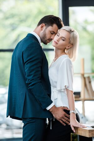 handsome bearded man touching attractive woman with closed eyes