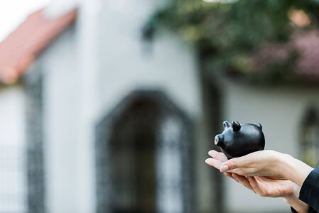 cropped view of woman holding black piggy bank near building
