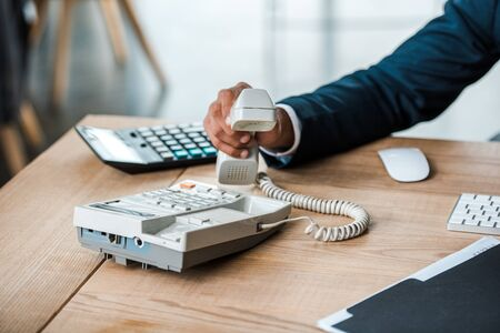 cropped view of businessman holding retro telephone in office