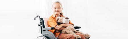 panoramic shot of smiling kid holding teddy bear and sitting on wheelchair