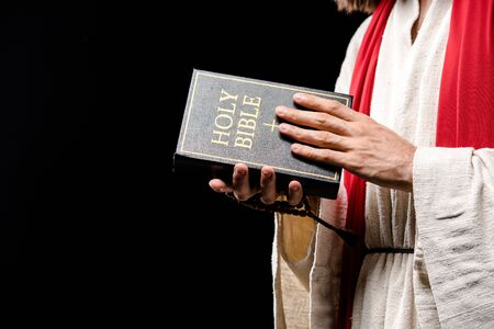 cropped view of holding holy bible isolated on black Stock Photo