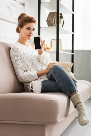 attractive woman in white sweater holding smartphone with copy space