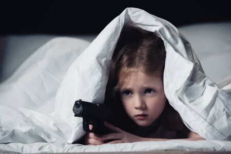 frightened child holding gun while hiding under blanket isolated on black