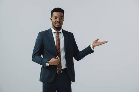 bel homme afro-américain en costume gesticulant isolé sur gris