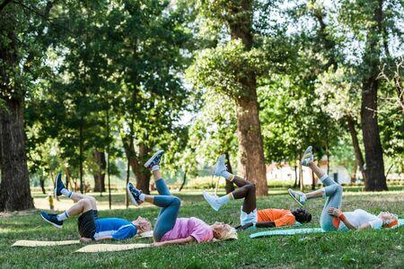 multicultural senior men and women exercising on fitness mats near trees Foto de archivo - 130204722