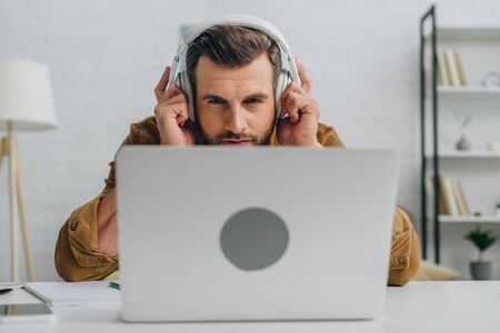 handsome man listening music and looking at screen of laptop