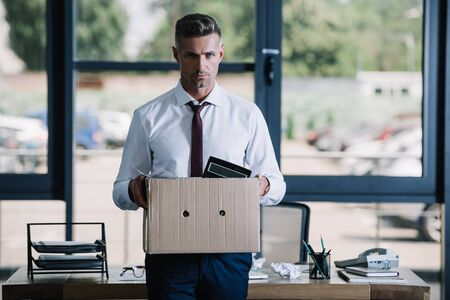 serious businessman holding box while looking at camera