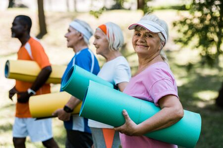 selective focus of happy retired woman in cap holding fitness mat near multicultural pensioners Foto de archivo - 130205191