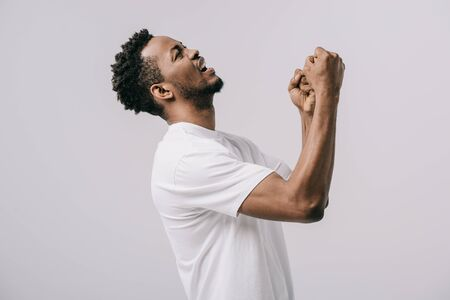 upset bearded african american man with clenched fists isolated on grey Stockfoto