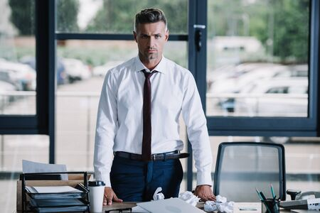 serious businessman looking at camera near desk in office