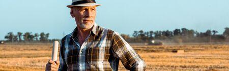 panoramic shot of self-employed man holding rake in wheat field