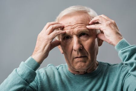 exhausted retired man looking at camera and touching head isolated on grey