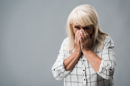 upset retired woman with grey hair covering face on grey