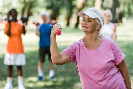 selective focus of senior woman in cap holding dumbbell while exercising near pensioners Foto de archivo - 130208819