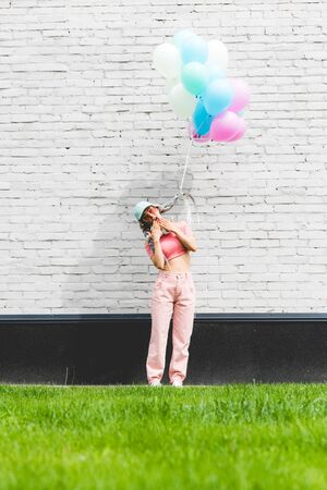 stylish girl with decorative balloons covering mouth near brick wall