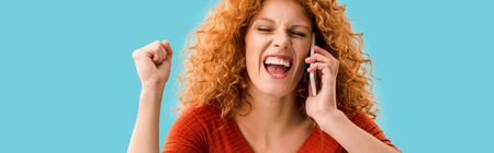 excited girl talking on smartphone isolated on blue