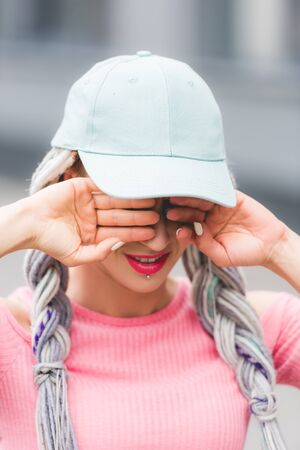 selective focus of stylish girl with dreadlocks in hat Covering Eyes with hands