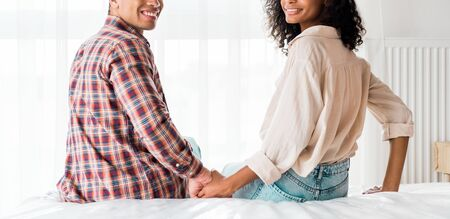 cropped view of african american husband and woman holding hand and looking at camera while sitting on bed Standard-Bild - 130209403