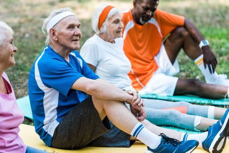 selective focus of multicultural senior men and women in sportswear sitting on fitness mats