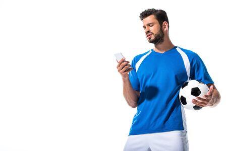 Fußballspieler mit Ball mit Smartphone isoliert auf weiss mit Kopienraum