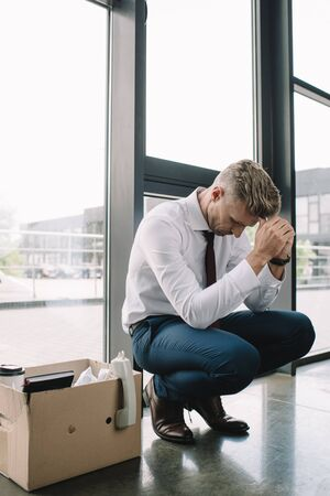 dismissed businessman sitting carton box in office