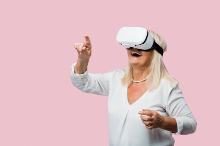 retired woman pointing with finger while wearing virtual reality headset isolated on pink