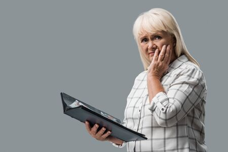 upset retired woman holding photo album and touching face isolated on grey Stockfoto