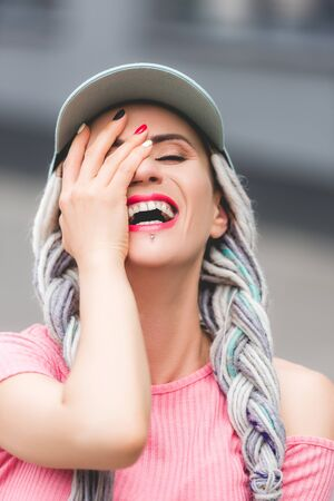 beautiful stylish girl with dreadlocks in hat laughing and covering face with hand