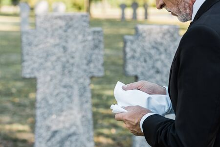 cropped view of senior man holding handkerchief in hands on graveyard