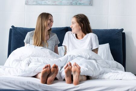 two smiling barefoot lesbians sitting on bed and looking at each other Stockfoto