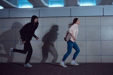 Frau läuft vor Dieb im Hoodie in Unterführung davon Standard-Bild
