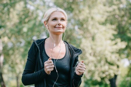 beautiful mature sportswoman looking away while running in park and listening music in earphones Standard-Bild