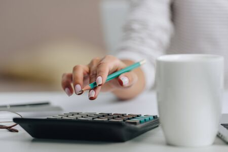 selective focus of woman holding pencil and calculating in apartment Reklamní fotografie