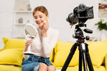 selective focus of smiling beauty blogger with mirror using decorative cosmetics in front of video camera