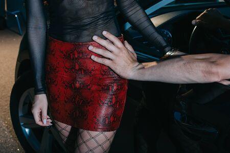 vista ritagliata dell'uomo che tocca seducente in gonna rossa in piedi vicino all'auto Archivio Fotografico